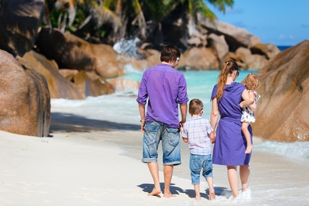 Portrait of young family with two kids walking along tropical beach photo