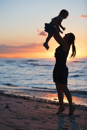 Mother and daughter silhouettes on beach at sunset photo