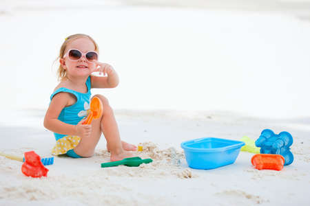 Adorable toddler girl playing with beach toys on white sand beach Stock Photo - 8703948