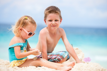 Brother and sister playing together on tropical beach photo