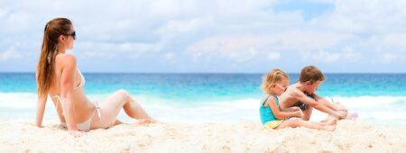 kids playing beach: Panoramic photo of young mother and her two kids at beach