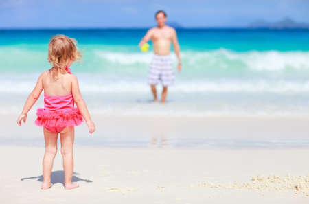 Back view of playful toddler girl on white sand beach with her father photo