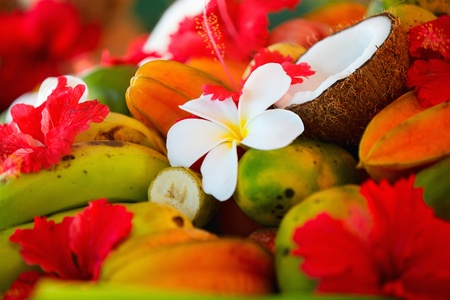 Several coconuts and tropical fruits decorated with frangipani and hibiscus flowers