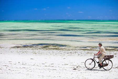 zanzibar: Jonge man met een fiets op tropische strand op het eiland Zanzibar