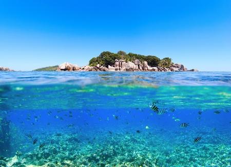 Onder en boven water foto van kleine eiland in Seychellen Stockfoto