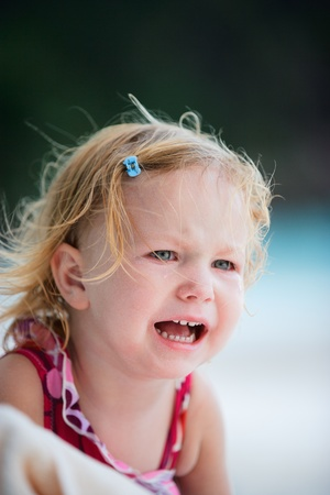 Outdoor portrait of cute crying toddler girl