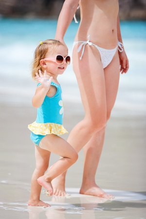 little girl swimsuit: Young mother and her adorable little daughter on beach vacation