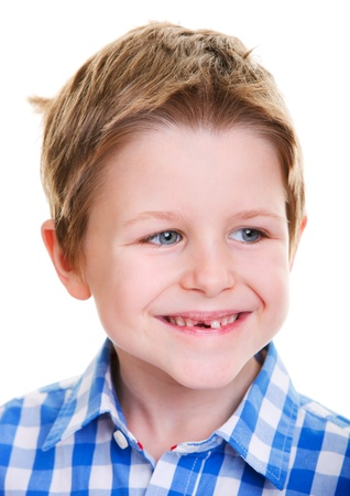 Studio portrait of cute 6 years old boy showing his missing tooth photo