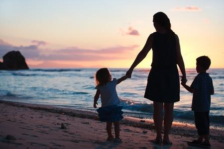 kind silhouet: Moeder en twee kinderen silhouetten op strand bij zons ondergang