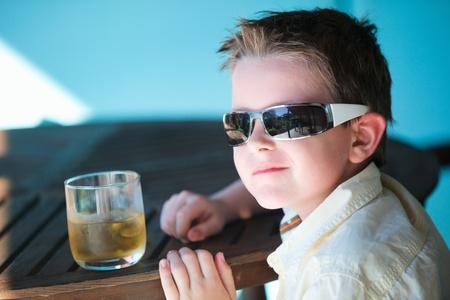 sole occhiali: Ritratto di elegante little boy in occhiali da sole bere succo di mela