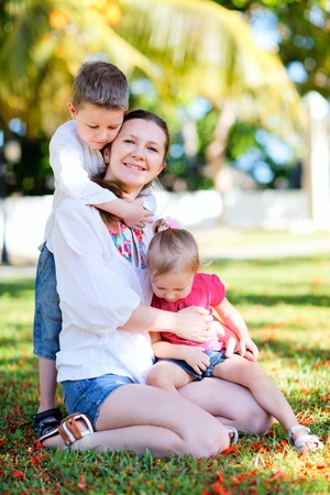 Summer family portrait of happy young mother with her two kids photo
