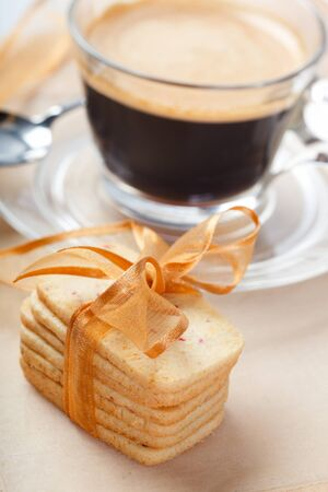 Stacked cookies decorated with bow and cup of fresh coffee photo