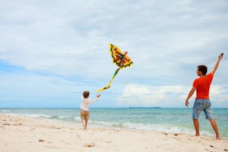 若い父と息子の凧と海岸を走っています