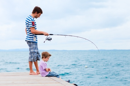 Young father and his son fishing together from wooden jetty Stock Photo - 9087283