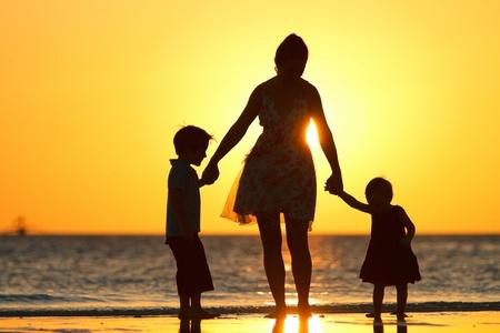 madre e hijo: Madre y siluetas de dos ni�os en la playa al atardecer