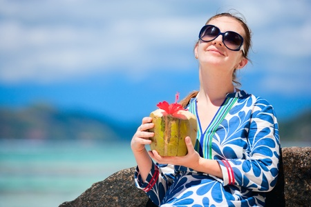 Portrait of young beautiful woman with coconut photo
