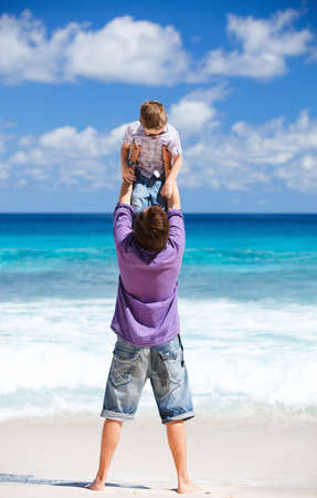 Young father with his son on beach vacation having fun photo