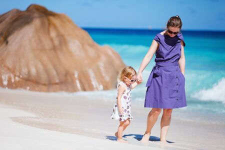 Young mother and her adorable daughter enjoying day at beach photo