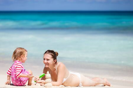 Mother and daughter playing with sand at tropical beach photo
