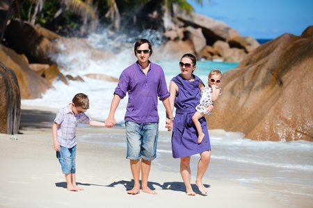 Young beautiful family of four walking along tropical beach Stock Photo - 9087555