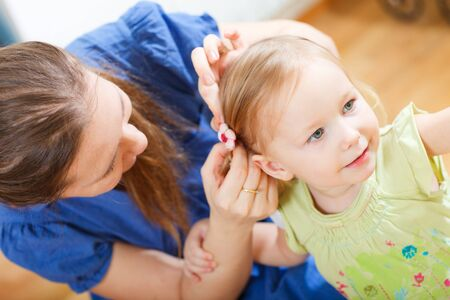 Portrait of young woman brushing her daughters hair photo