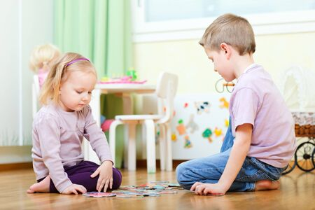 Brother and his little sister at home working on puzzle Stock Photo - 9166026