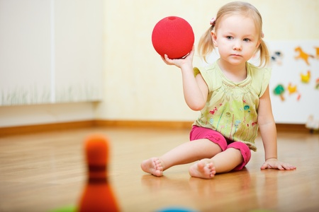 Adorable toddler girl playing bowling at home photo