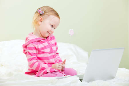 Closeup of adorable little girl sitting with laptop photo