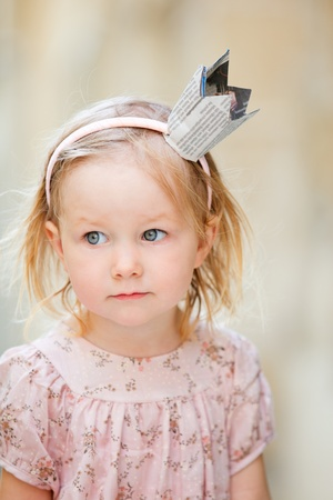 Portrait of very cute little princess outdoors photo