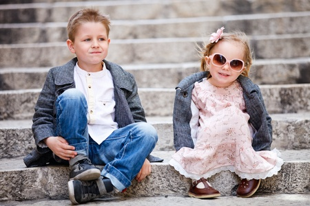 little boy and girl: Brother and sister outdoors in city on beautiful spring day