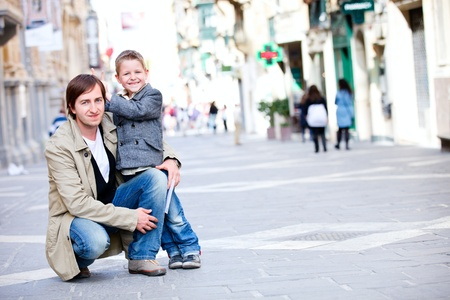 Happy father and son outdoors in city on beautiful spring day photo