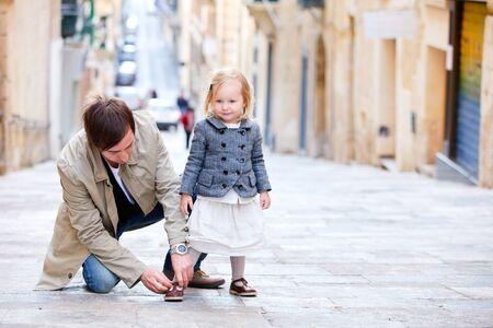 toddler walking: Father and his little daughter outdoors in city on sunny spring day