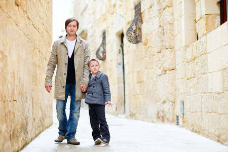 Father and son walking outdoors in city on beautiful spring day photo