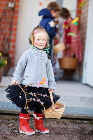 Adorable little girl outdoors collecting chocolate eggs as part of Easter tradition in Finland photo