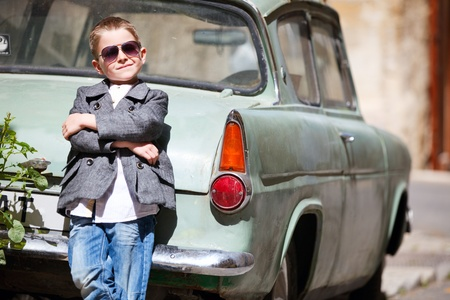 vintage children: Six years old boy outdoors in citystandimg near old car
