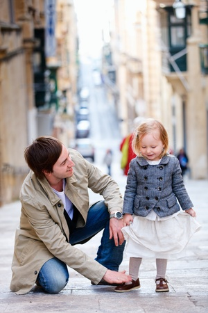 infant girl: Father and his little daughter outdoors in city