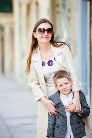 Mother and son outdoors in city on sunny spring day photo
