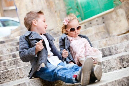 Brother and sister outdoors in city on beautiful spring day photo