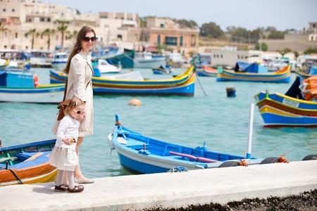 malta: Mother and her little daughter walking in Marsaxlokk village in Malta Stock Photo