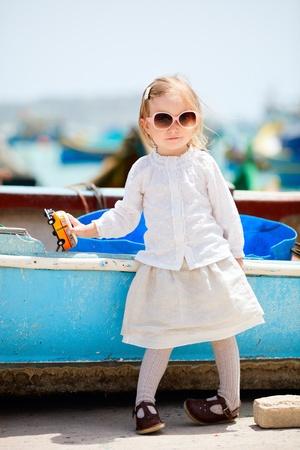 playing with baby: Cute girl little giocando con autobus Maltese giallo souvenir giocattolo