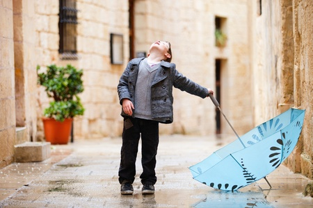 autumn rain: Cute little boy with umbrella looking up to sky Stock Photo