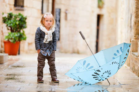Adorable little girl outdoors on rainy day photo