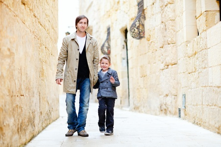 Father and son walking in city along narrow street photo