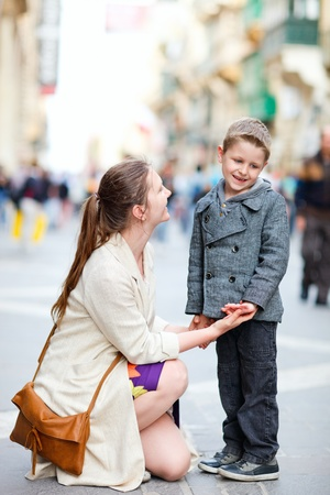 Young mother and her son outdoors on city street photo