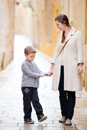 Young mother and her son outdoors on city street in Mdina, Malta photo
