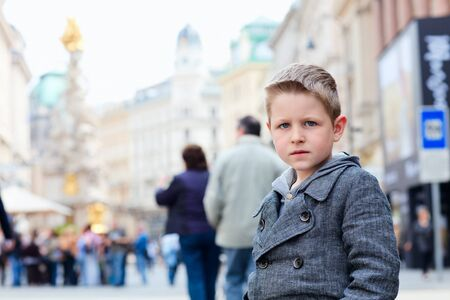 Cute little boy portrait at busy street in city photo
