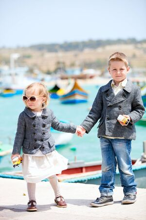 Two little kids near harbor in little charming village of Marsaxlokk in Malta photo