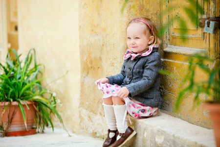 little town: Adorable little girl outdoors sitting near door and old yellow wall