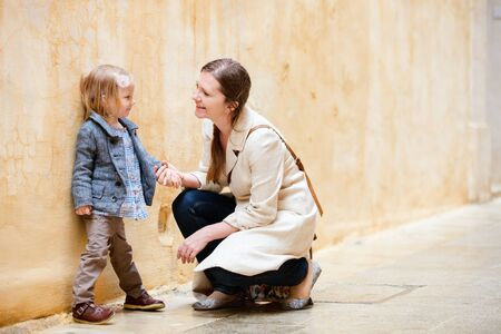 Mother and her little daughter outdoors in city photo