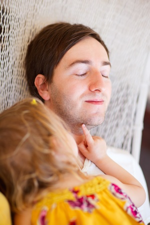 Father and his little daughter relaxing in hammock photo